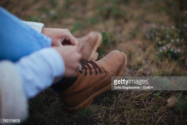 low section of woman tying boots - leather boot stock pictures, royalty-free photos & images