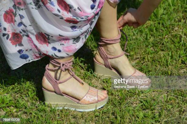 Low Section Of Woman Tying Sandal Lace On Grassy Field