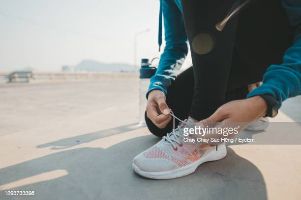 low section of woman tying shoe lace on road - tying shoelace stock pictures, royalty-free photos & images