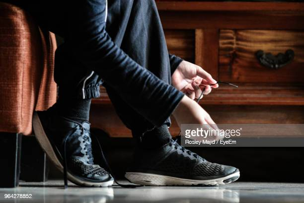 low section of woman tying shoelace at home - tying shoelace stock pictures, royalty-free photos & images