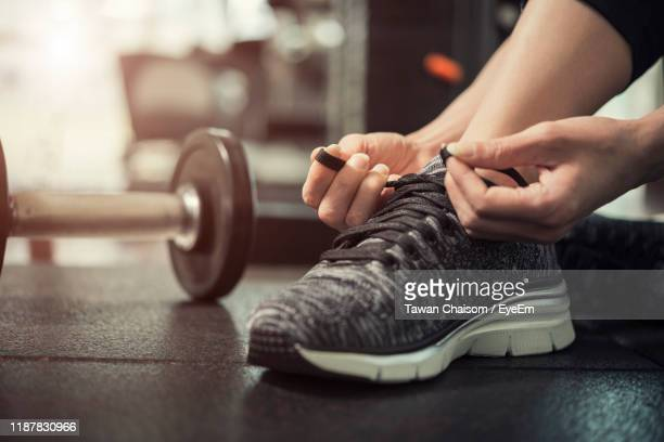 low section of woman tying shoelace in gym - tying shoelace stock pictures, royalty-free photos & images