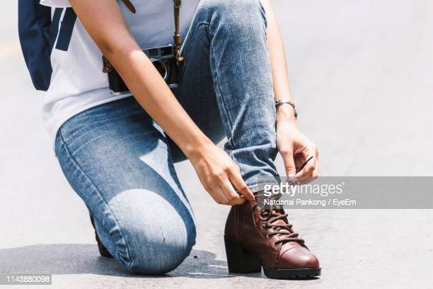 low section of woman tying shoelace on road during sunny day - brown shoe stock photos and pictures