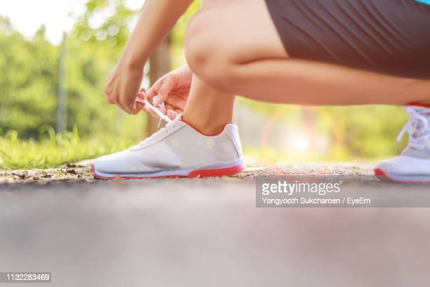 low section of woman tying shoelace on road - tying shoelace stock pictures, royalty-free photos & images