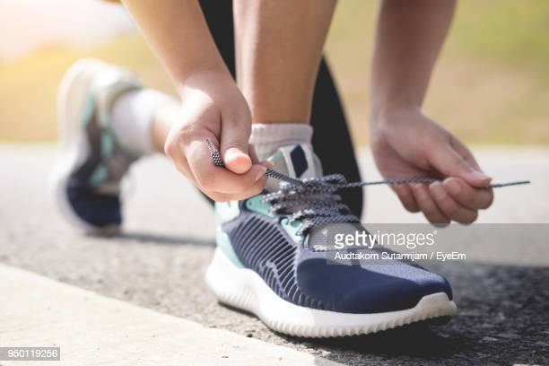 low section of woman tying shoelace on road - sports shoe stock pictures, royalty-free photos & images
