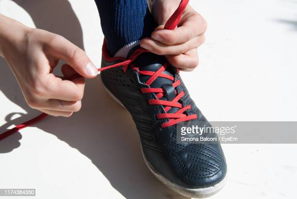 low section of woman tying shoelace on table - tying shoelace stock pictures, royalty-free photos & images
