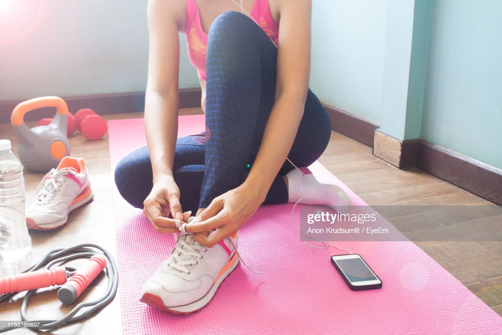 Low Section Of Woman Tying Shoelace While Sitting On Exercise Mat At Home : Foto de stock