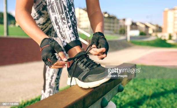 low section of woman tying shoelaces while exercising at park - tighten stock pictures, royalty-free photos & images