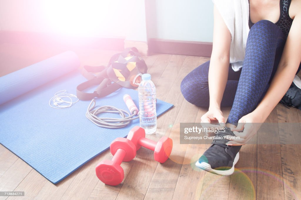 Low Section Of Woman Tying Shoes : Stock Photo