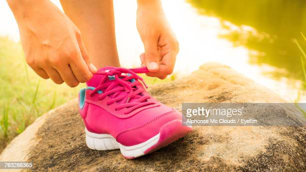 low section of woman tying sports shoelace on rock - pink shoe stock pictures, royalty-free photos & images