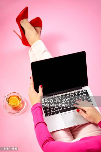 low section of woman using laptop while sitting on pink background - roze achtergrond stockfoto's en -beelden