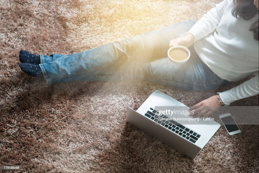 Low Section Of Woman Using Laptop While Sitting On Rug At Home : Stock-Foto