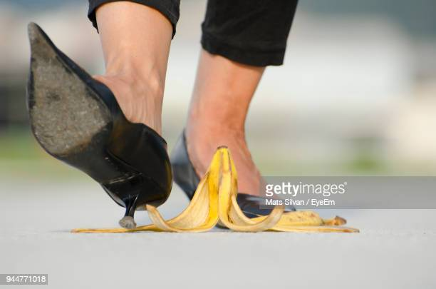 Low Section Of Woman Walking By Banana Peel On Footpath