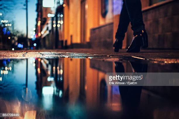 low section of woman walking by puddle at sidewalk - puddle stock pictures, royalty-free photos & images