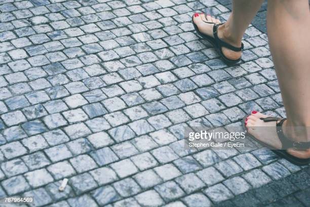 Low Section Of Woman Walking On Cobblestoned Footpath