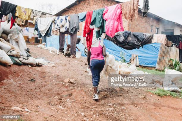 low section of woman walking on field in slum - slum stock photos and pictures