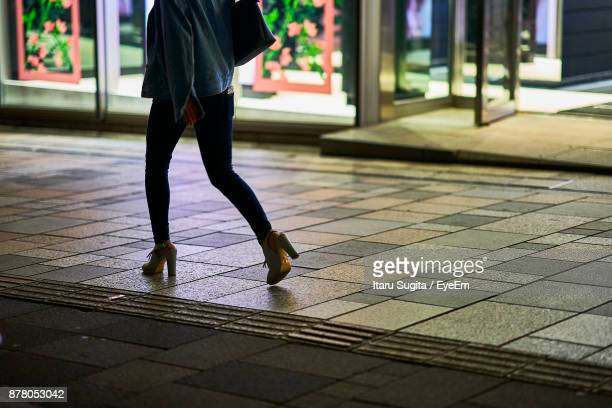 Low Section Of Woman Walking On Footpath At Night