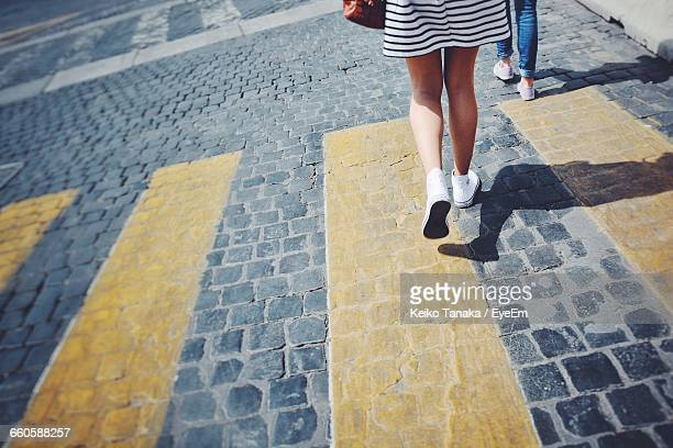 Low Section Of Woman Walking On Footpath During Sunny Day