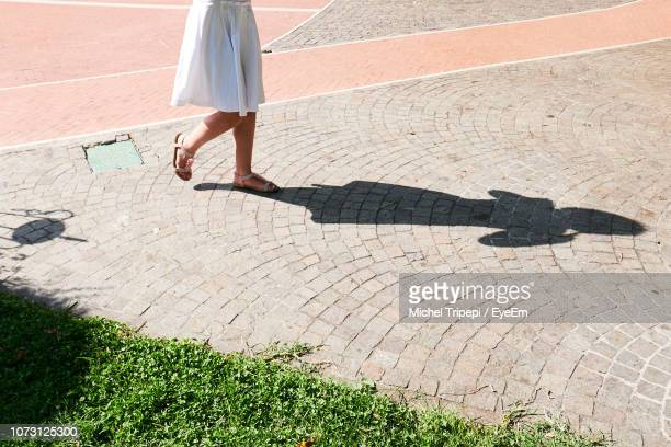 low section of woman walking on footpath - 人の脚 ストックフォトと画像