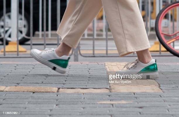low section of woman walking on footpath - sezione inferiore foto e immagini stock