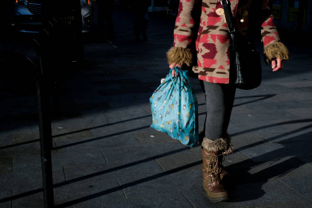 Low Section Of Woman Walking On Footpath With Shopping Bag