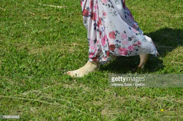 Low Section Of Woman Walking On Grassy Field
