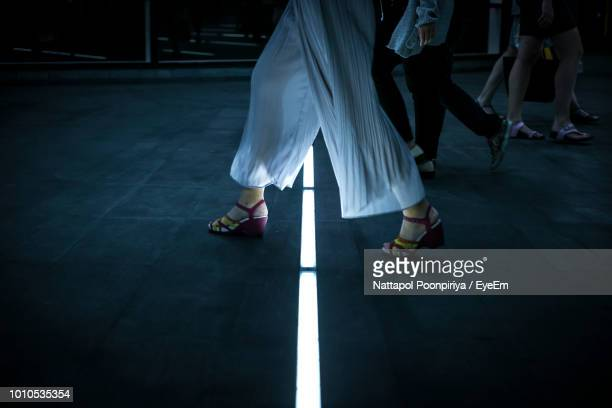Low Section Of Woman Walking On Illuminated Street At Night