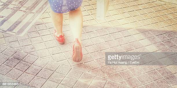 low section of woman walking on paving footpath - 人の脚 ストックフォトと画像