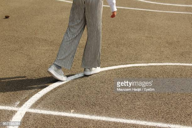Low Section Of Woman Walking On Playing Field