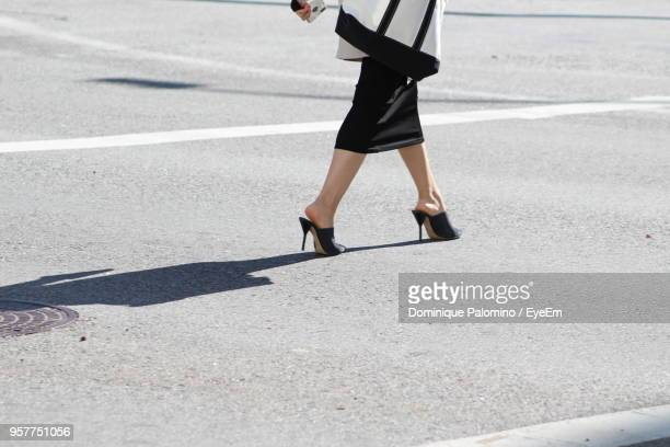 Low Section Of Woman Walking On Road During Sunny Day