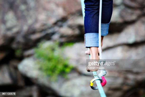 low section of woman walking on rope against rocks - 綱渡りのロープ ストックフォトと画像