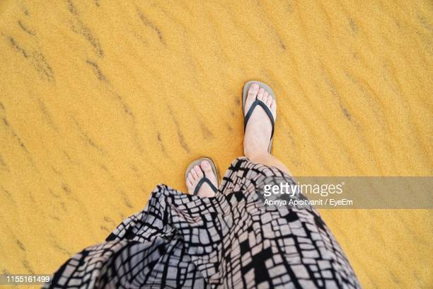 low section of woman walking on sand at beach - toe stock pictures, royalty-free photos & images