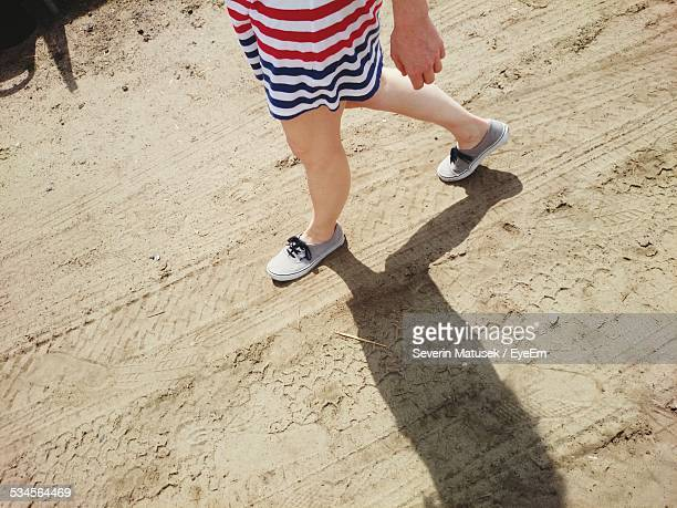 low section of woman walking on sand - sundress stock pictures, royalty-free photos & images