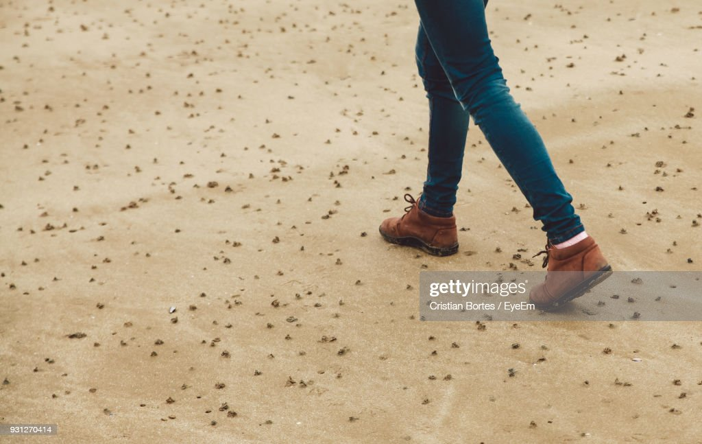 Low Section Of Woman Walking On Sand : Stock Photo