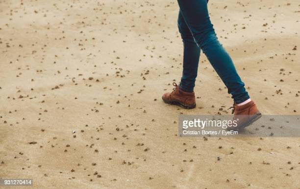 Low Section Of Woman Walking On Sand