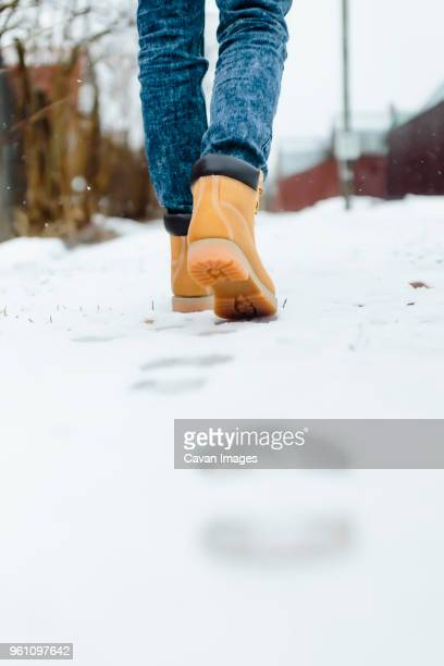 low section of woman walking on snow covered footpath - snow boot stock photos and pictures