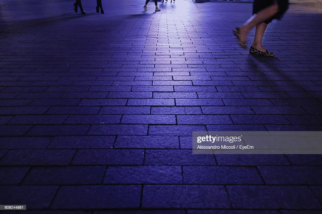 Low Section Of Woman Walking On Street At Night : Stock Photo