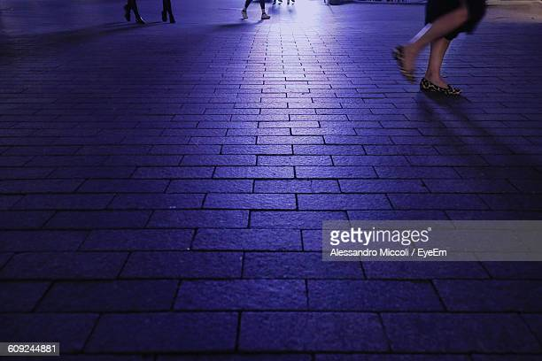 low section of woman walking on street at night - alessandro miccoli stockfoto's en -beelden