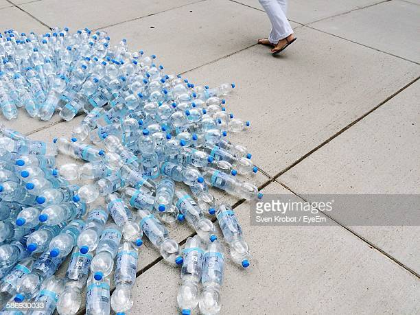 Low Section Of Woman Walking On Street By Water Bottles