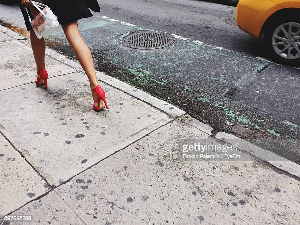 low section of woman walking on street - high heels stock pictures, royalty-free photos & images