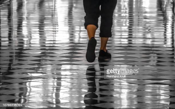 low section of woman walking on tiled floor - parte inferior imagens e fotografias de stock