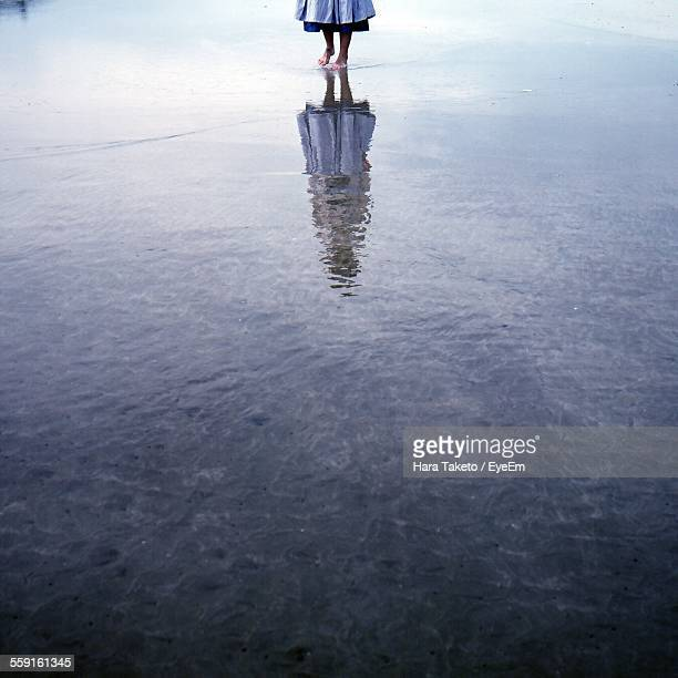 Low Section Of Woman Walking On Water With Reflection