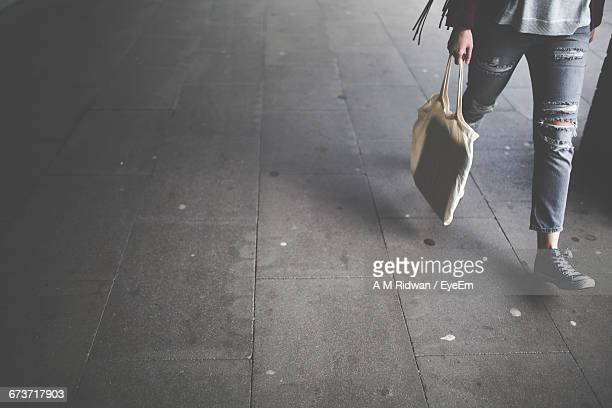 Low Section Of Woman Walking With Bag On Footpath