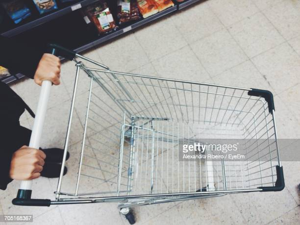 Low Section Of Woman Walking With Shopping Cart On Floor In Supermarket