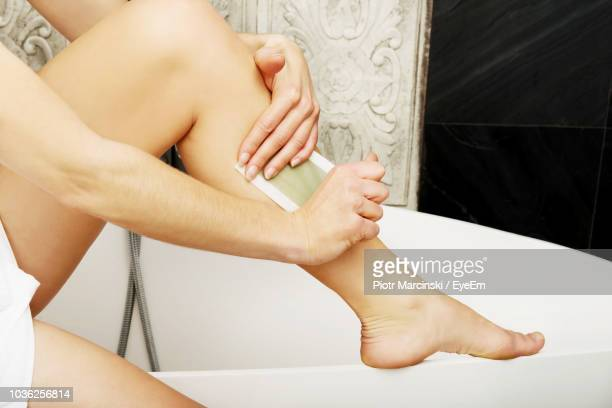 low section of woman waxing leg on bathtub in bathroom - leg waxing stock pictures, royalty-free photos & images