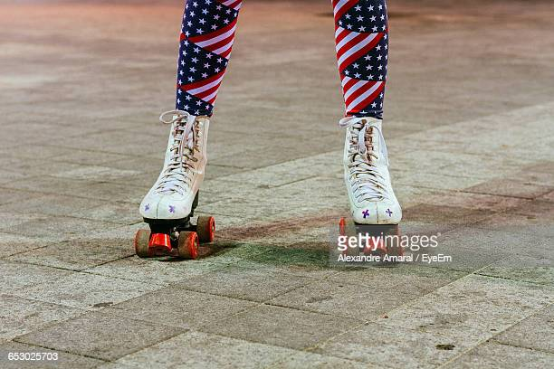 Low Section Of Woman Wearing American Flag Leggings While Roller Skating On Footpath