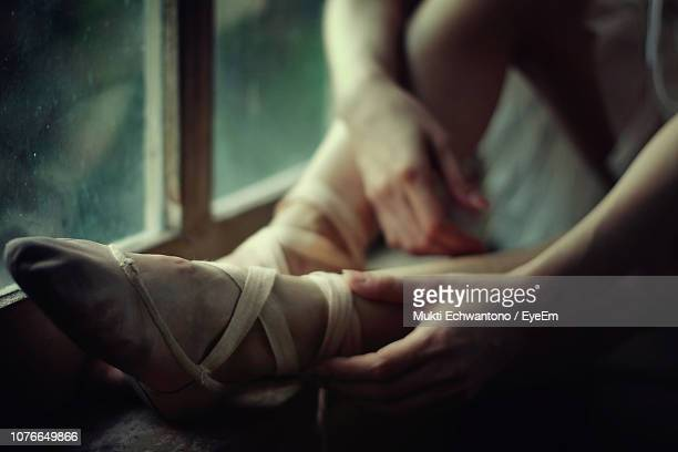 low section of woman wearing ballet shoe while sitting on window sill - バレリーナ ストックフォトと画像