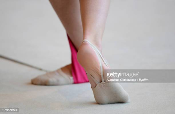 Low Section Of Woman Wearing Ballet Shoes On Floor
