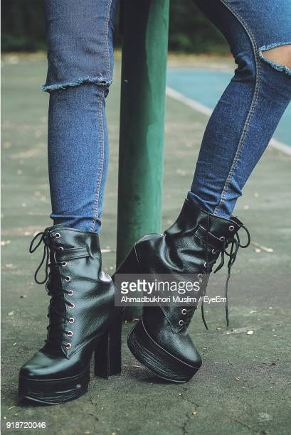 low section of woman wearing black boots on footpath - black boot stock pictures, royalty-free photos & images