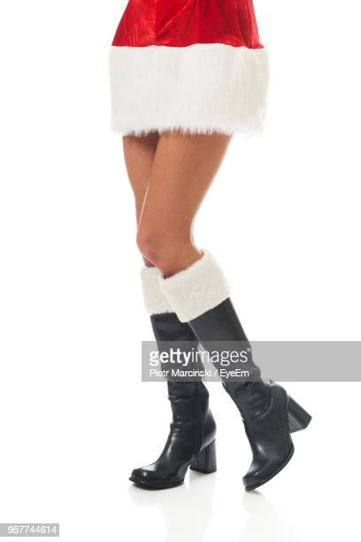 Low Section Of Woman Wearing Black Boots While Standing Against White Background