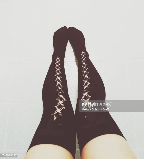 Low Section Of Woman Wearing Black Kneesock On Floor